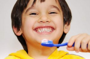 Child brushing teeth with a smile
