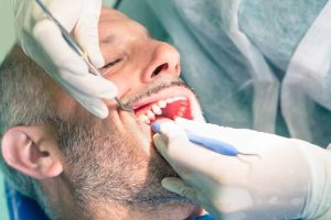 Patient getting plaque scraped off teeth